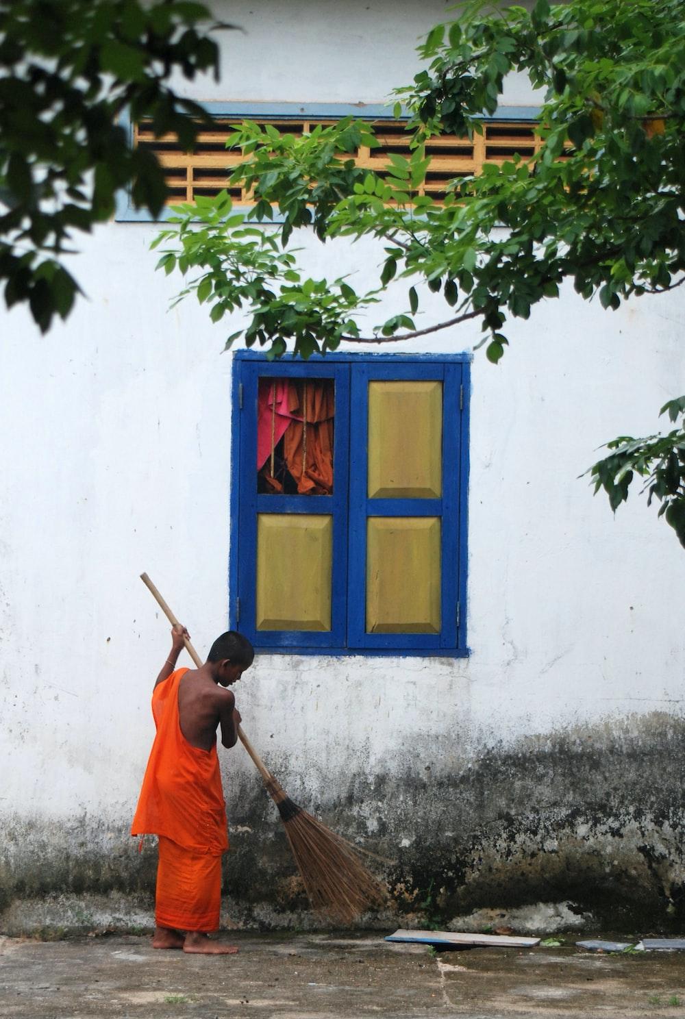 man in orange robe sitting beside blue wooden window