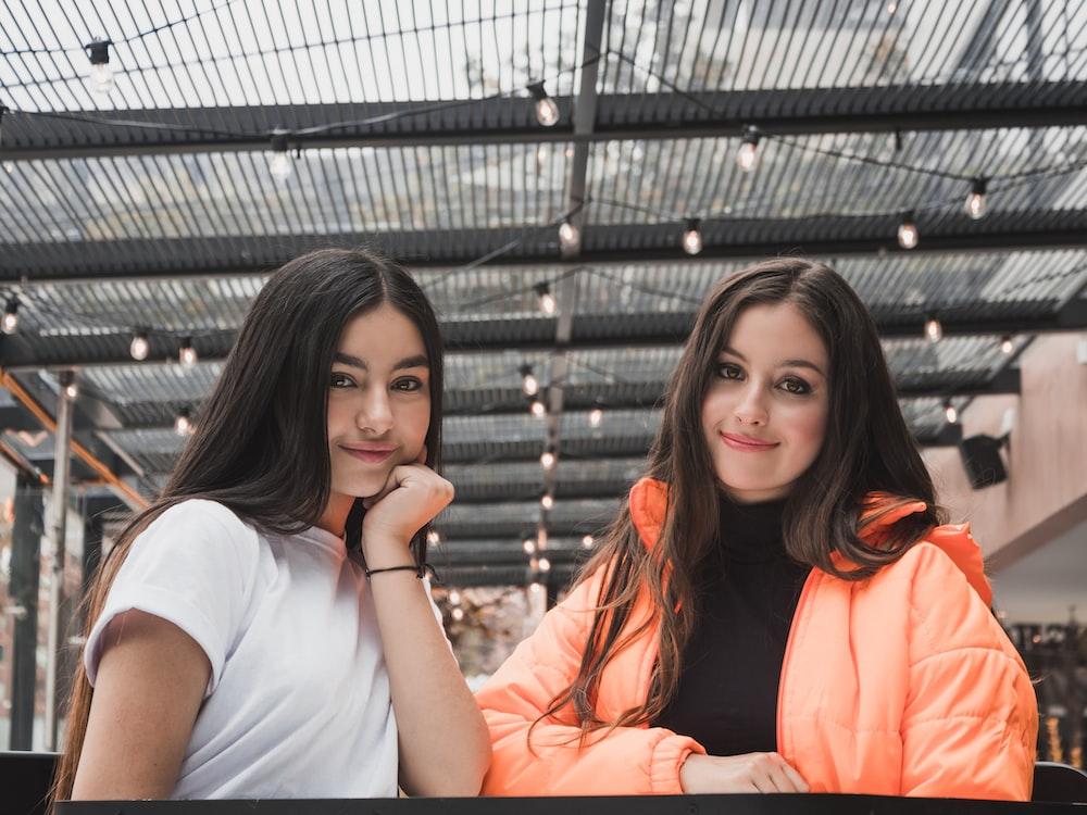woman in white t-shirt beside woman in orange jacket