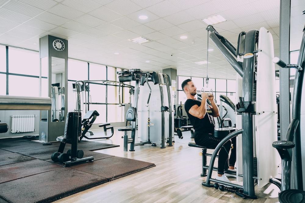 woman in black tank top and black pants exercising