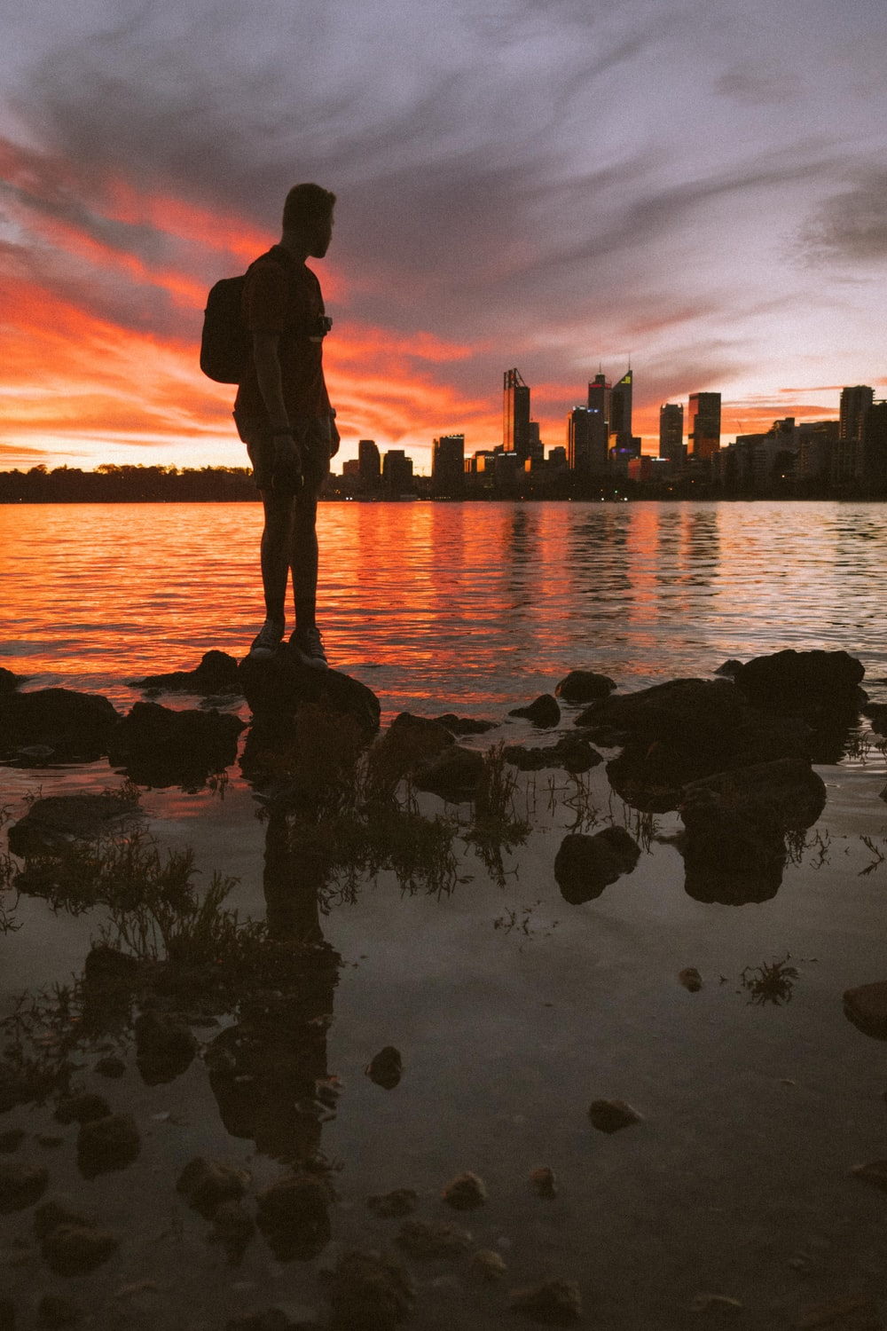 silhouette of man standing on rock near body of water during sunset