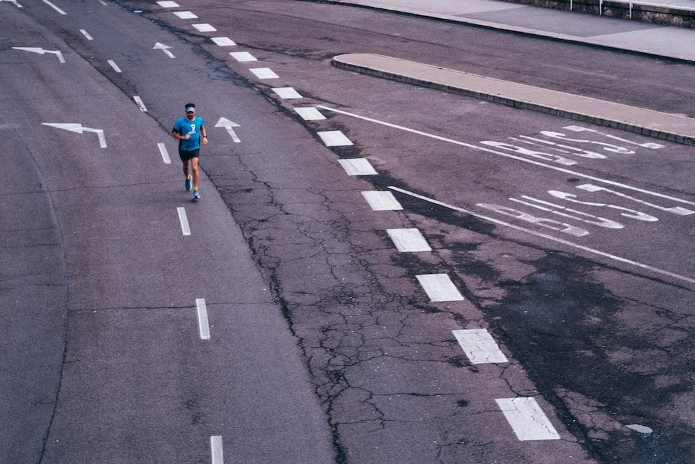woman in red jacket walking on pedestrian lane during daytime