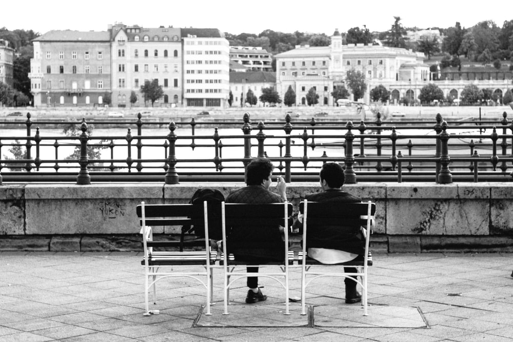 grayscale photo of 2 men sitting on chair