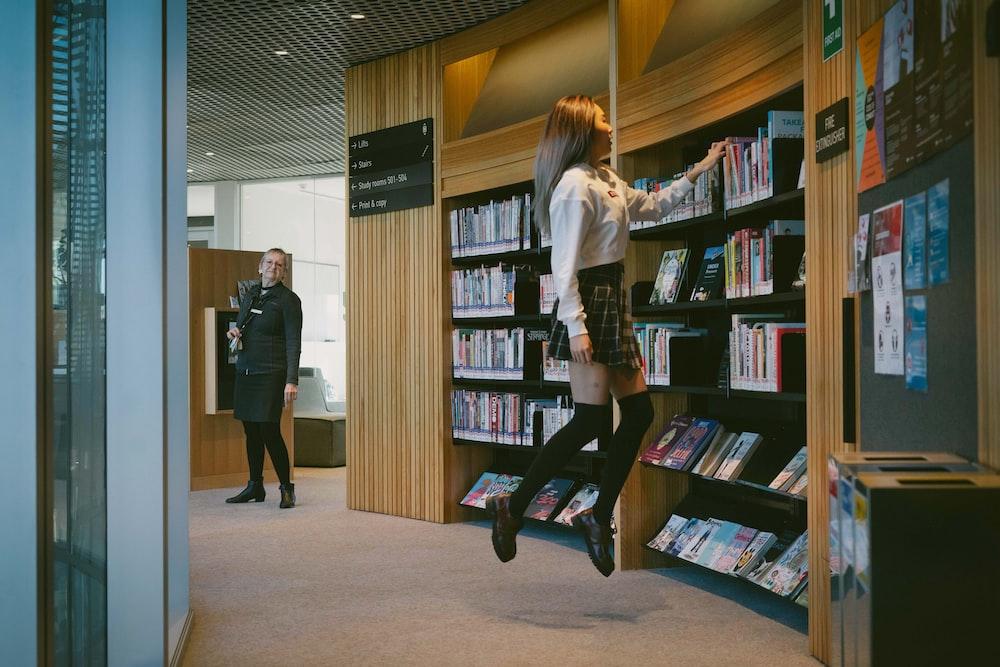 2 women standing near brown wooden book shelves