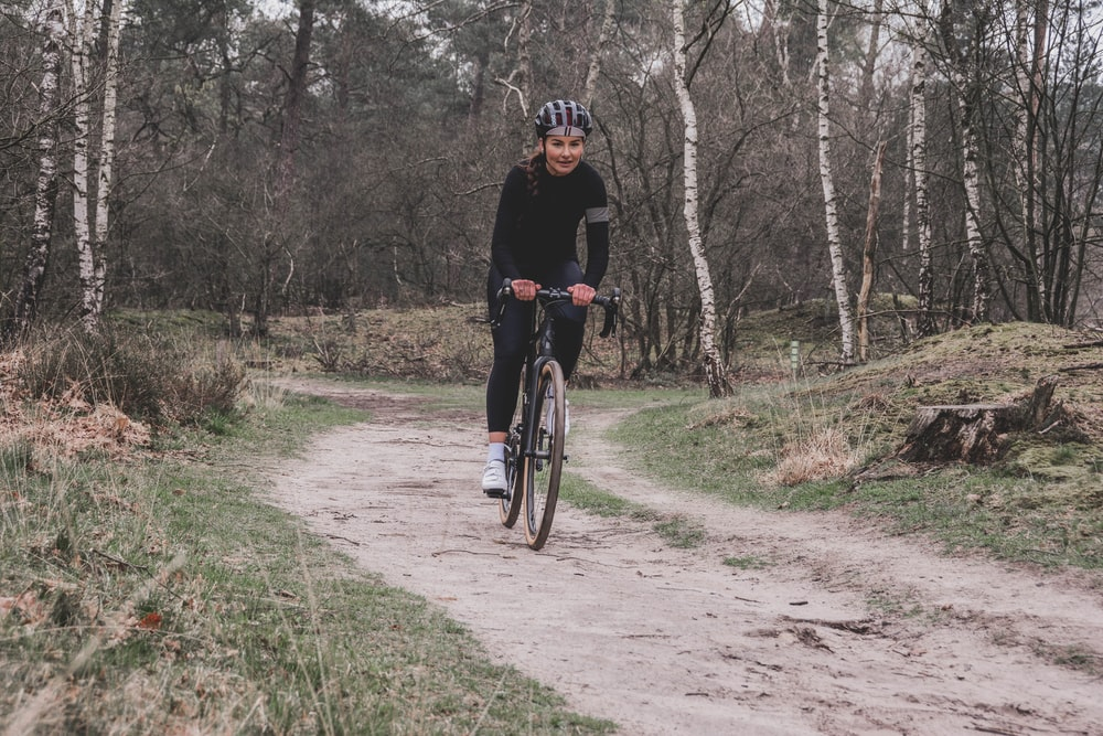 man in black jacket riding bicycle on dirt road during daytime