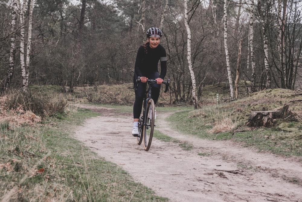 man in black jacket riding bicycle on dirt road during daytime