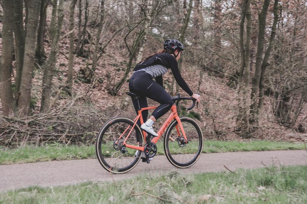 man in black jacket riding red bicycle