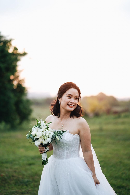 woman in white spaghetti strap dress holding white flower bouquet