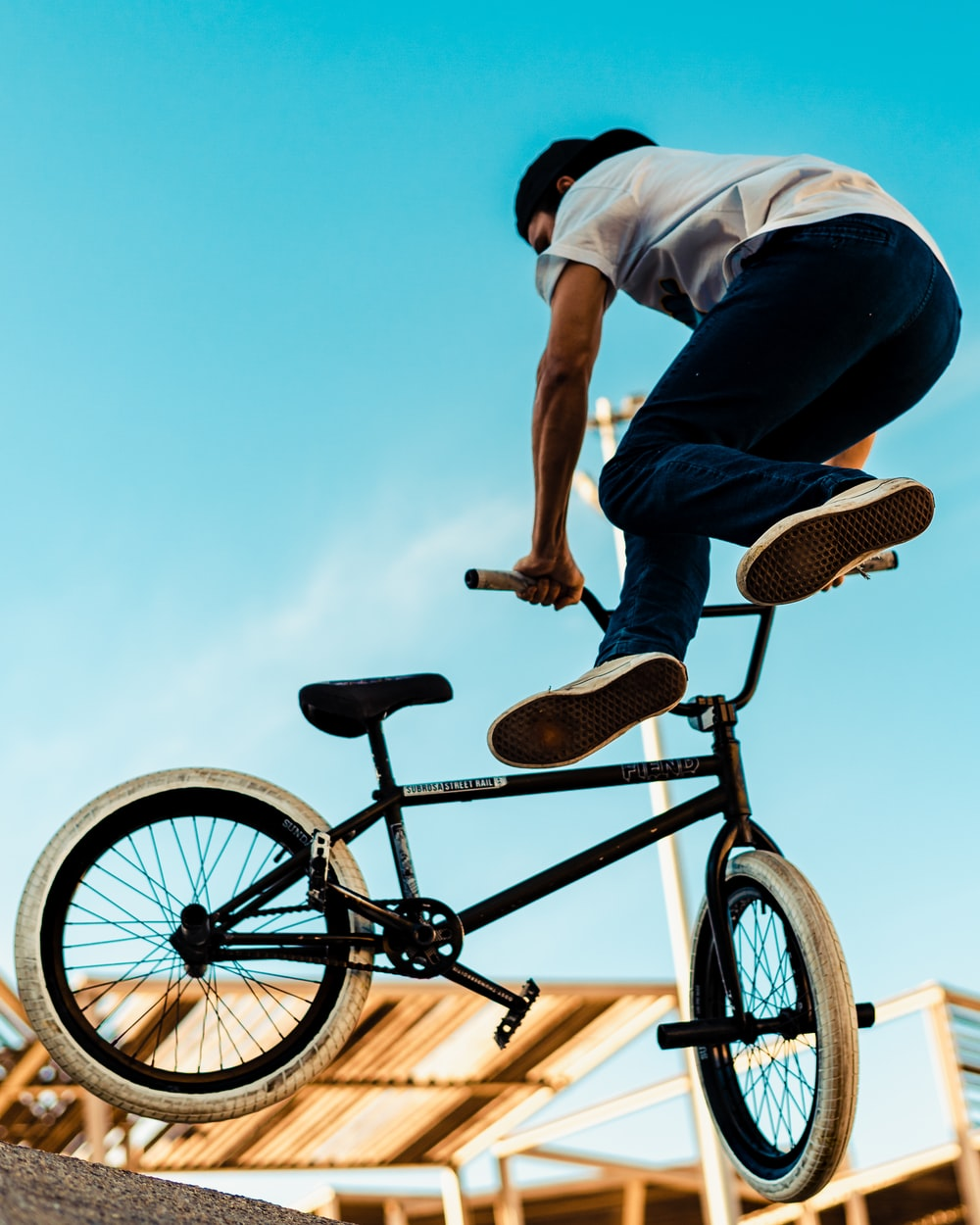 man in blue t-shirt riding on black bicycle