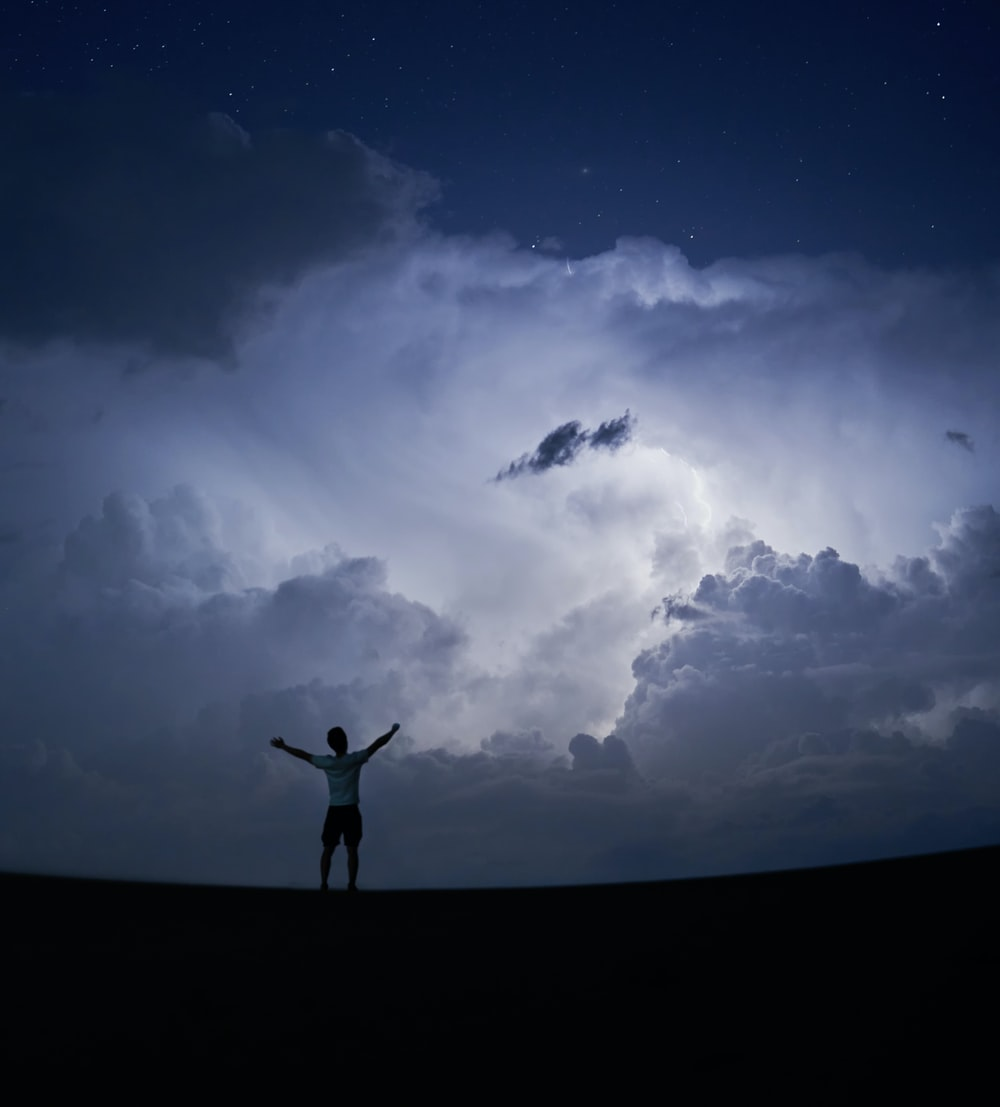 silhouette of person standing under blue sky and white clouds during daytime