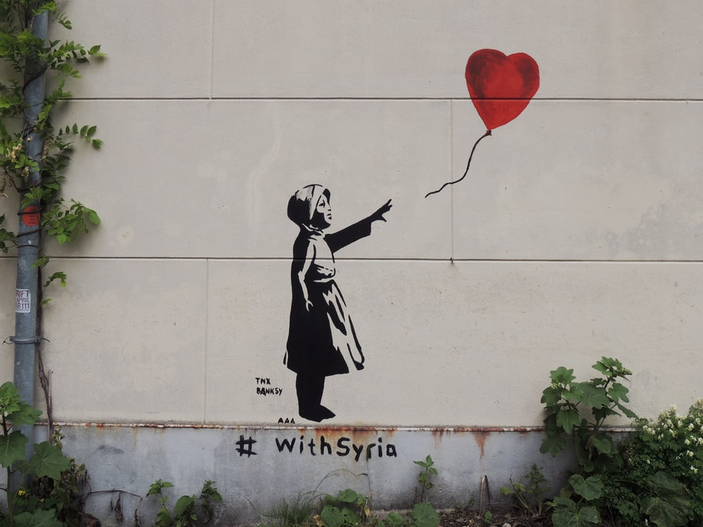 man in black suit holding red balloon