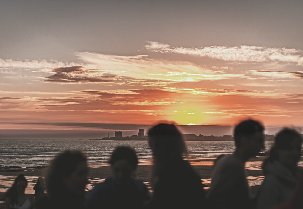 silhouette of people standing on seashore during sunset