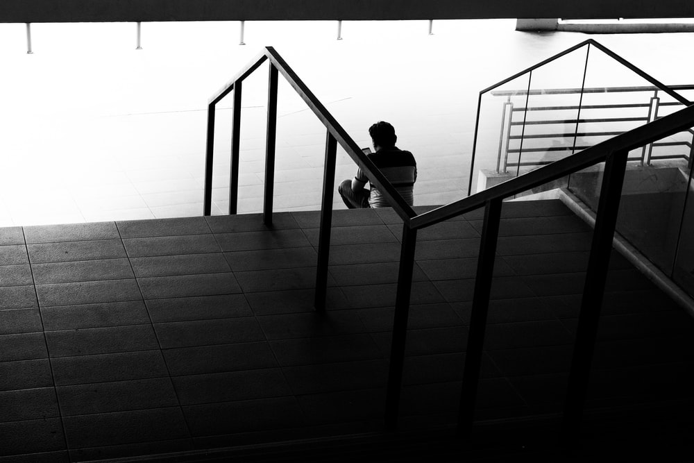 man in black shirt sitting on staircase