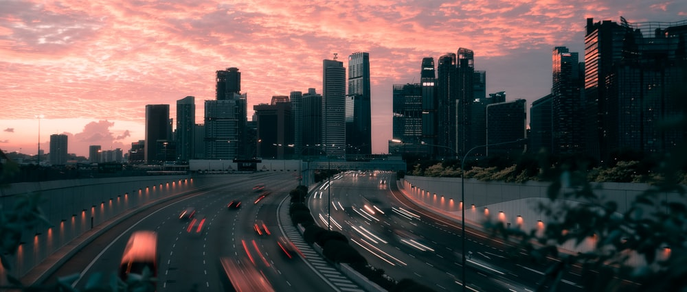 cars on road near city buildings during sunset