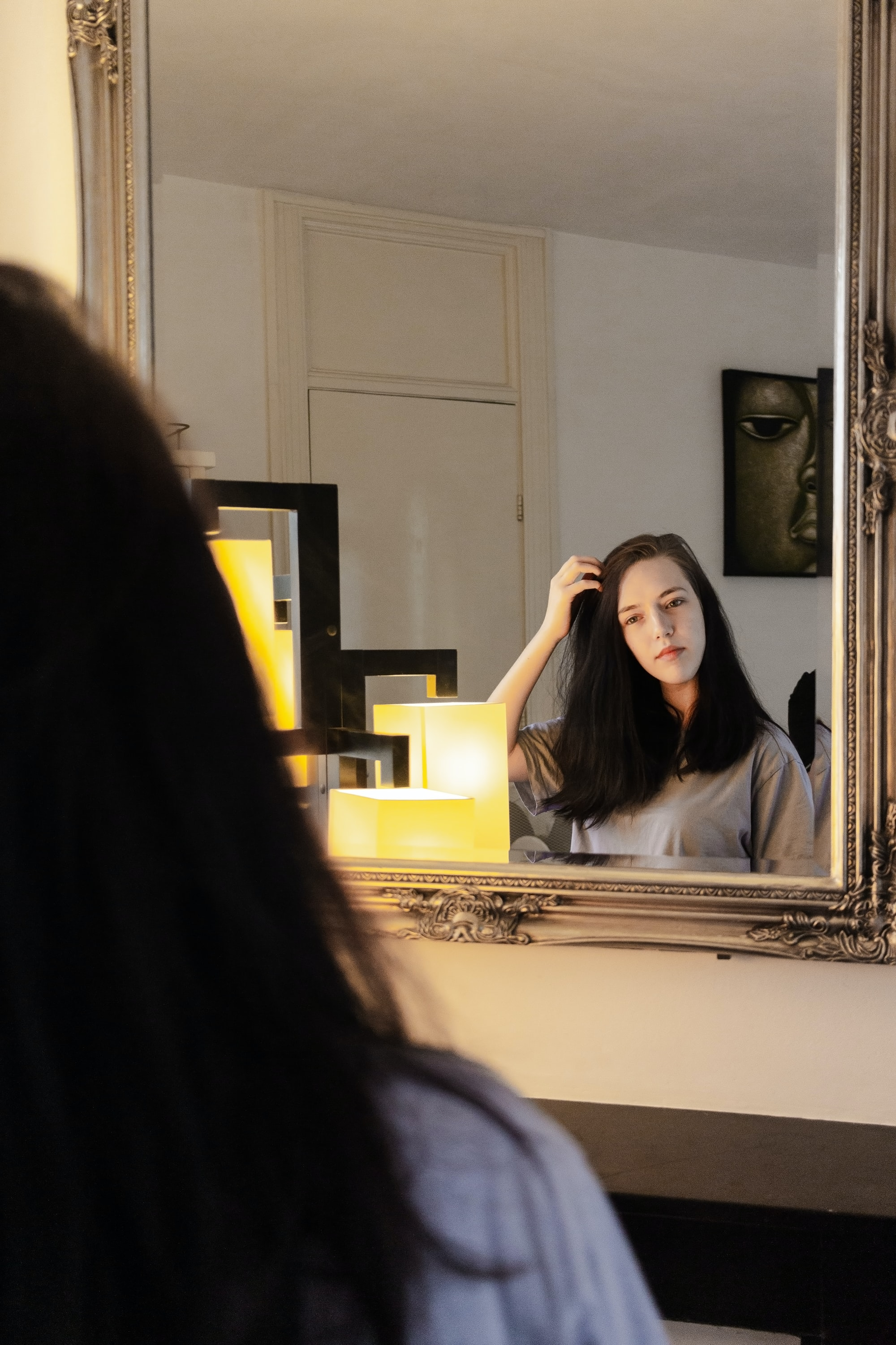 Girl with Black hair looking into mirror in a hotel room