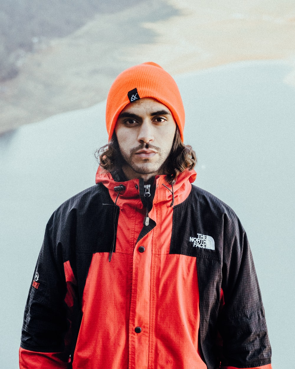 man in black and red zip up jacket and orange knit cap