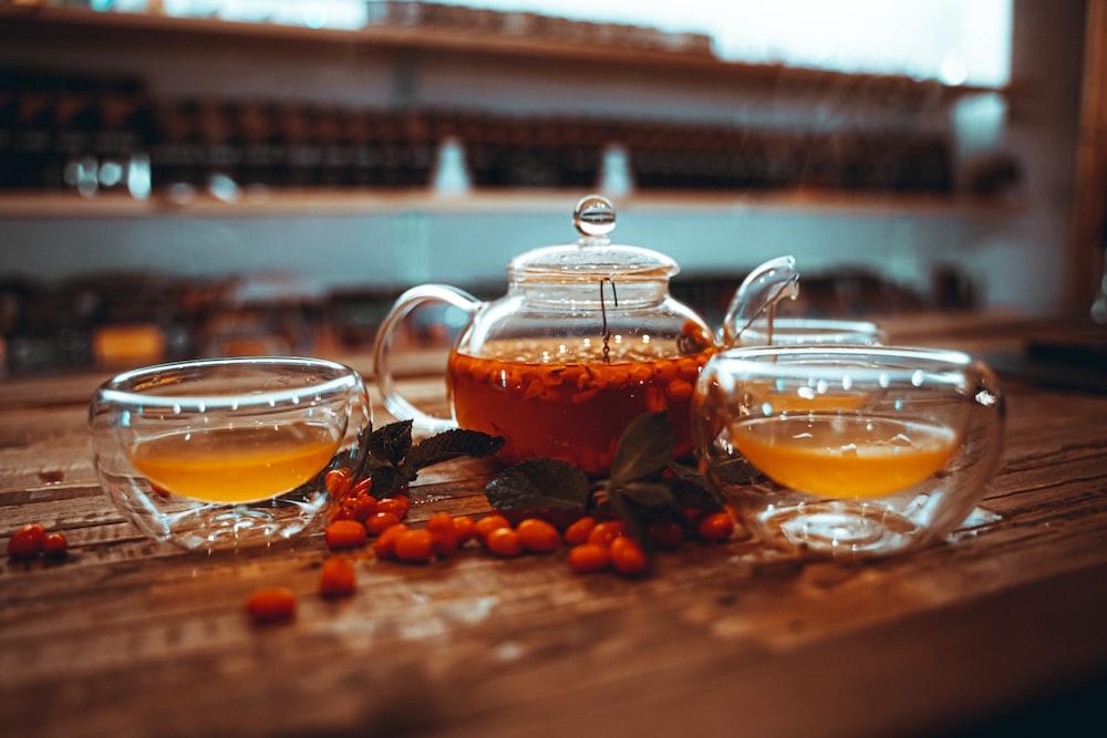 clear glass teapot with orange liquid