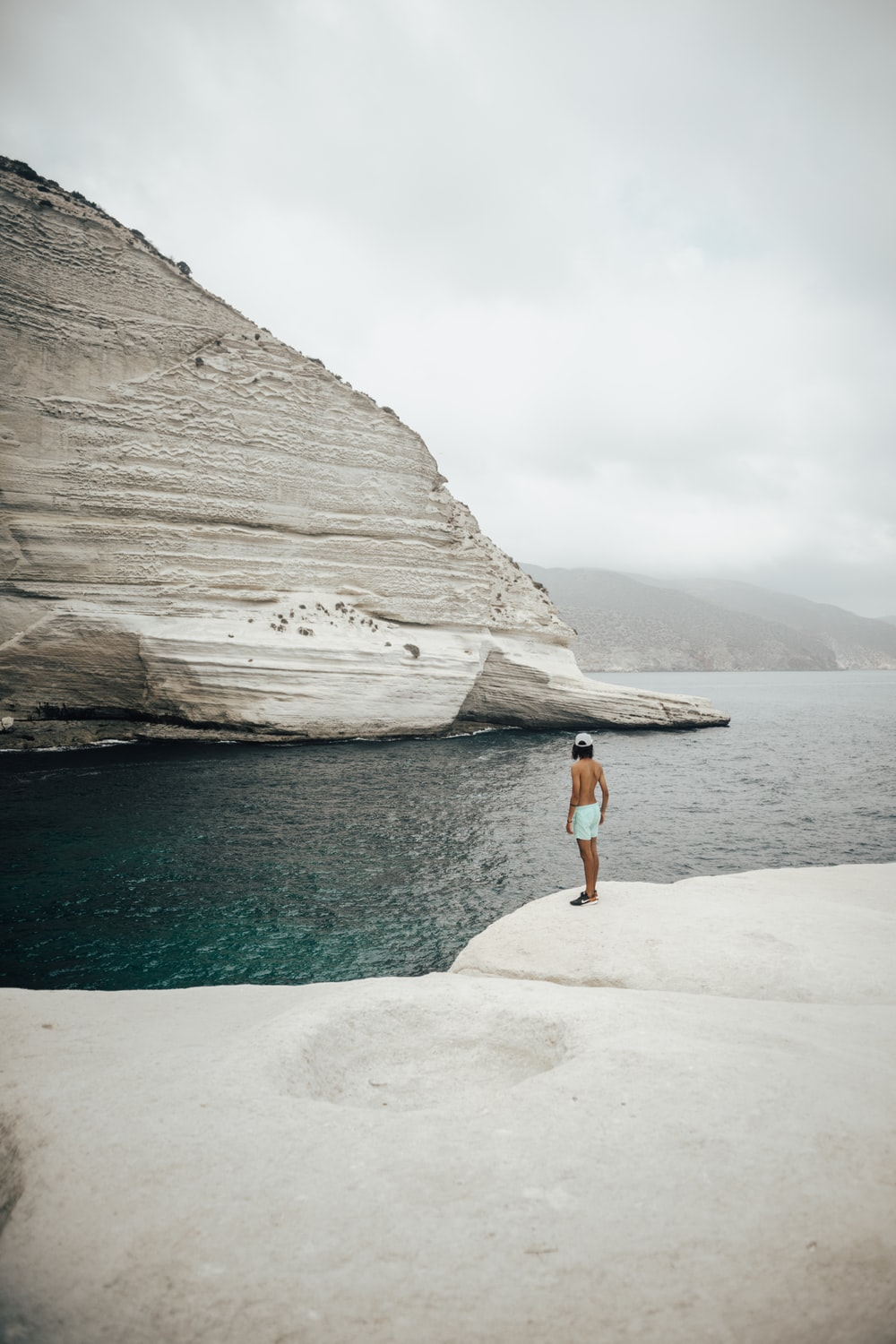 woman in blue denim shorts standing on rock formation near body of water during daytime