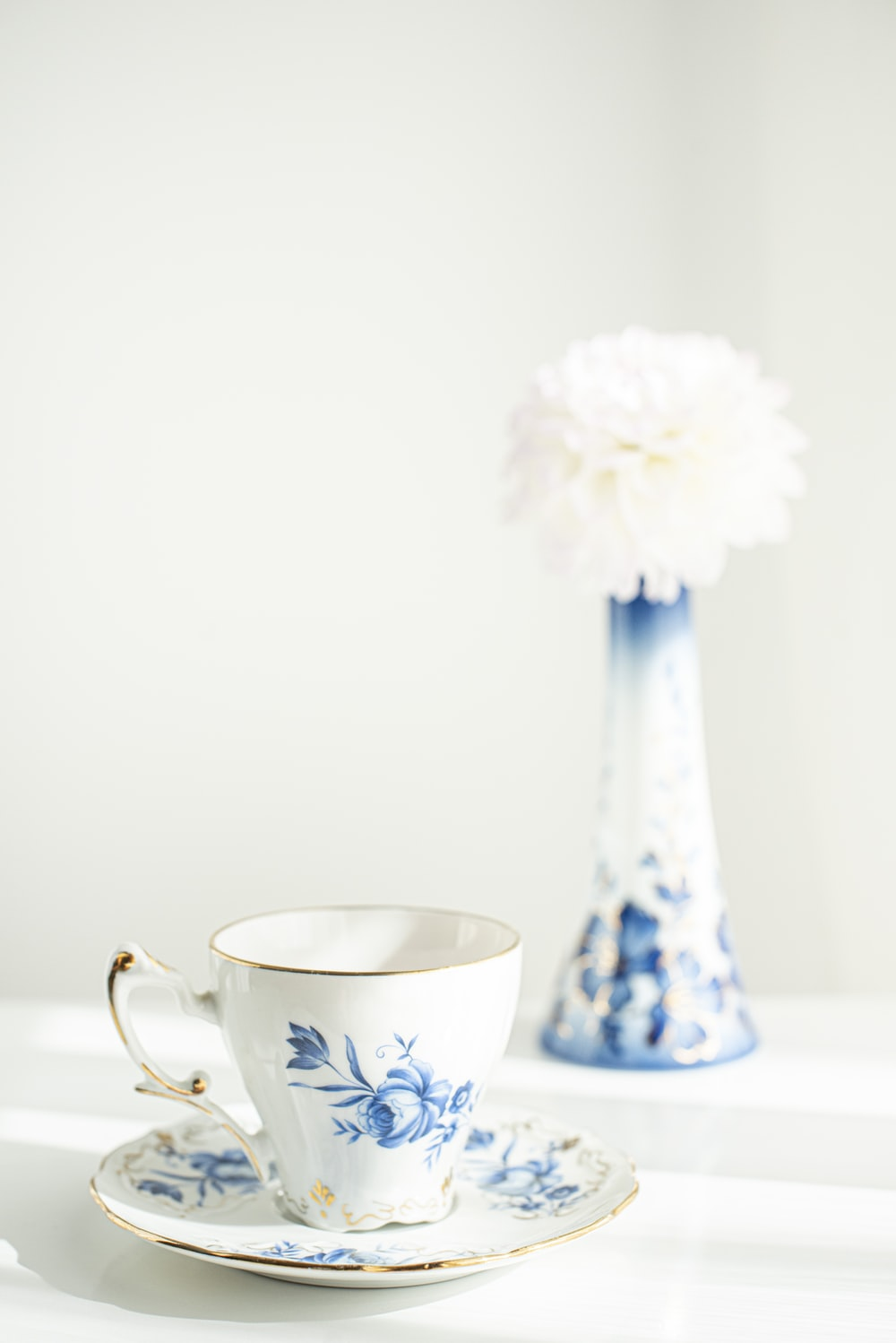 white and blue floral ceramic teacup with white flower