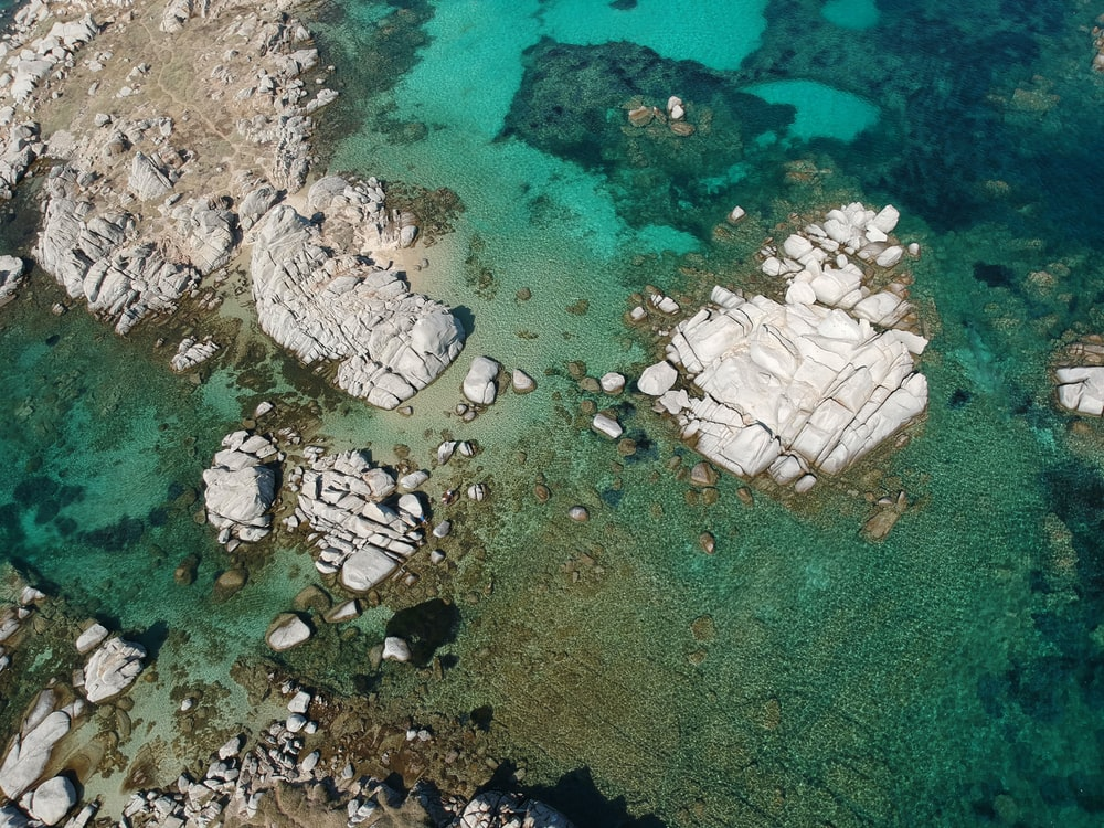 aerial view of white and gray rocks on body of water during daytime