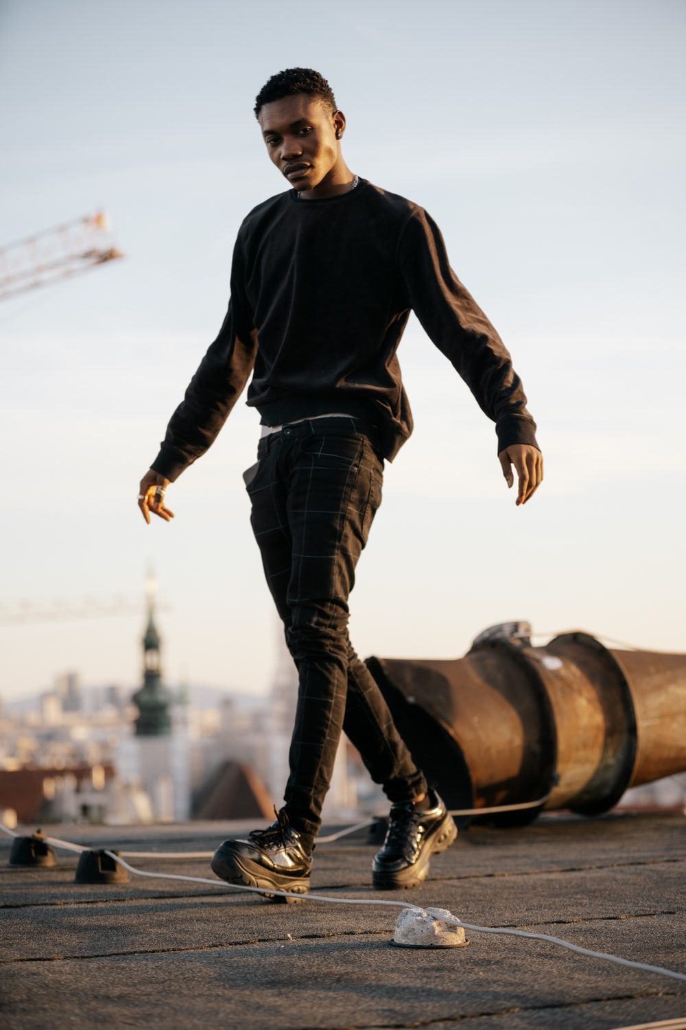 man in black long sleeve shirt and blue denim jeans standing on brown metal pipe during