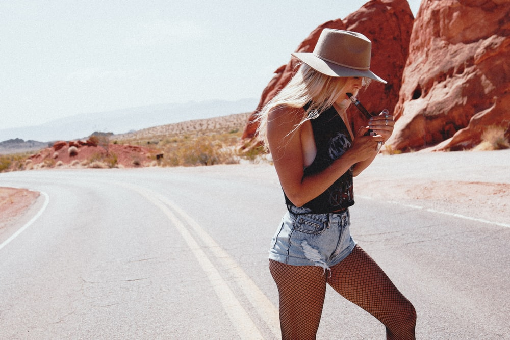 woman in black tank top and white denim shorts standing on road during daytime