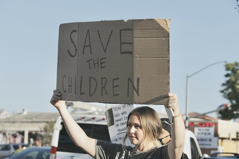 woman in black t-shirt holding brown cardboard box