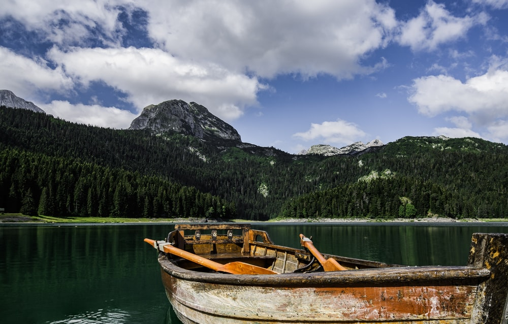 brown and white boat on lake near green mountain under blue and white cloudy sky during