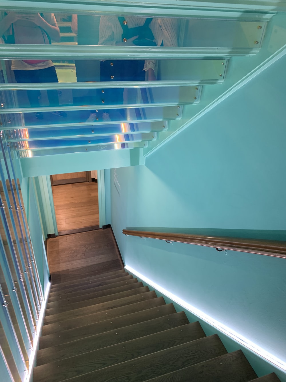brown wooden staircase with blue railings