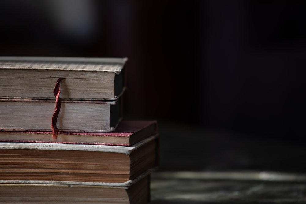 brown hardbound books on black table