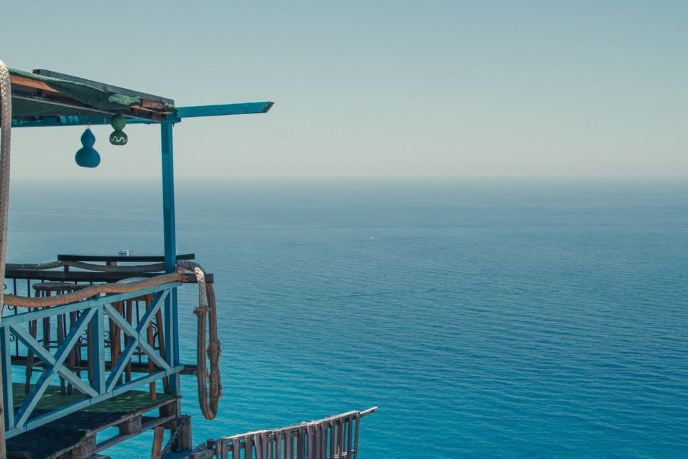 blue and brown wooden lifeguard tower on blue sea during daytime
