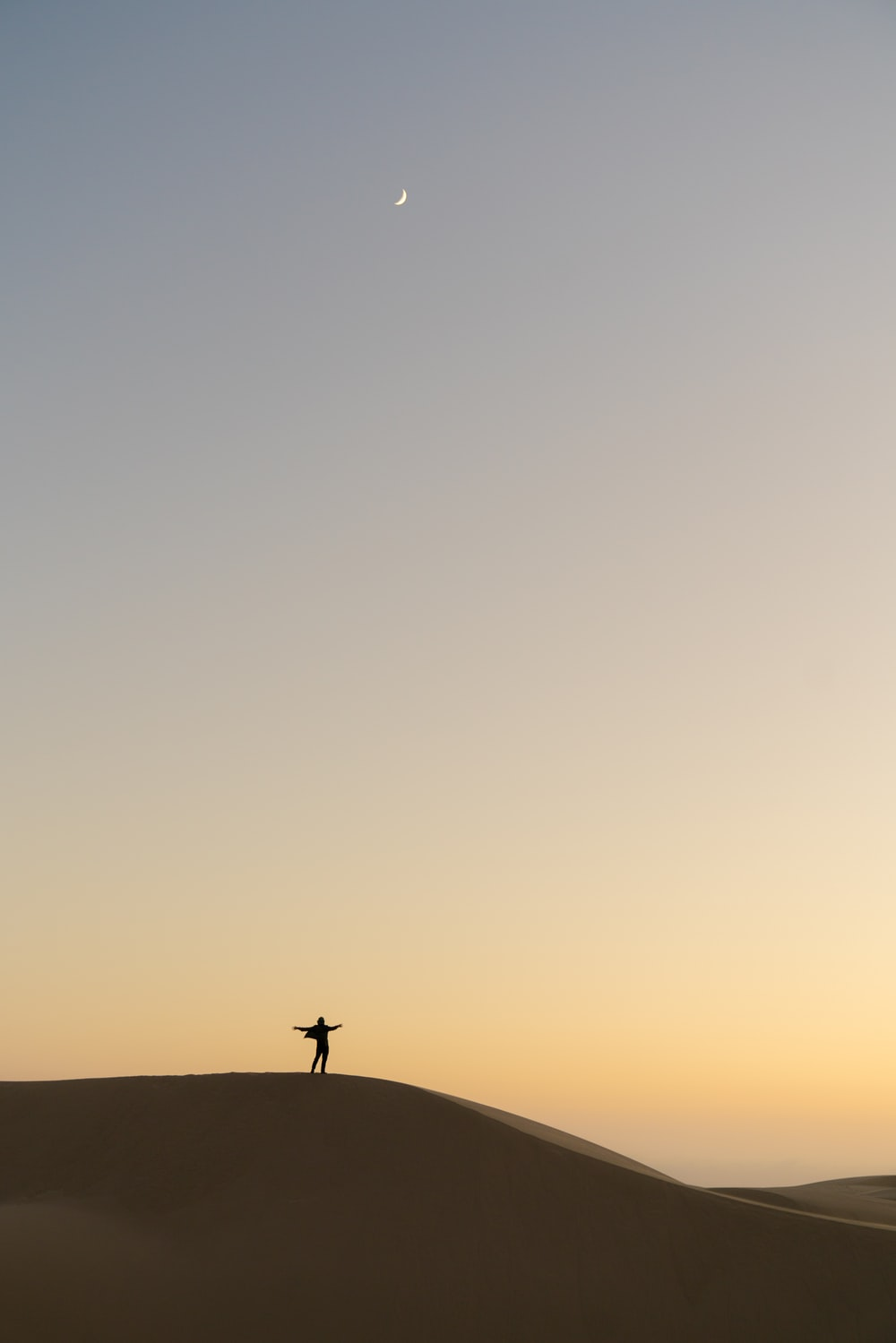 silhouette of man standing on sand during sunset