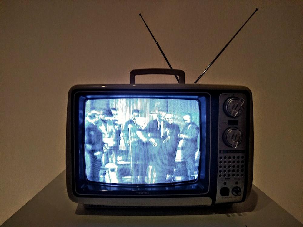 black crt tv turned on on white table