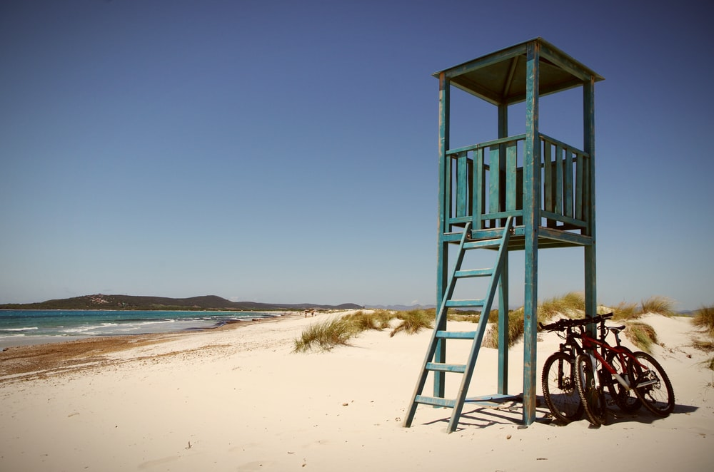 brown wooden lifeguard tower on beach during daytime