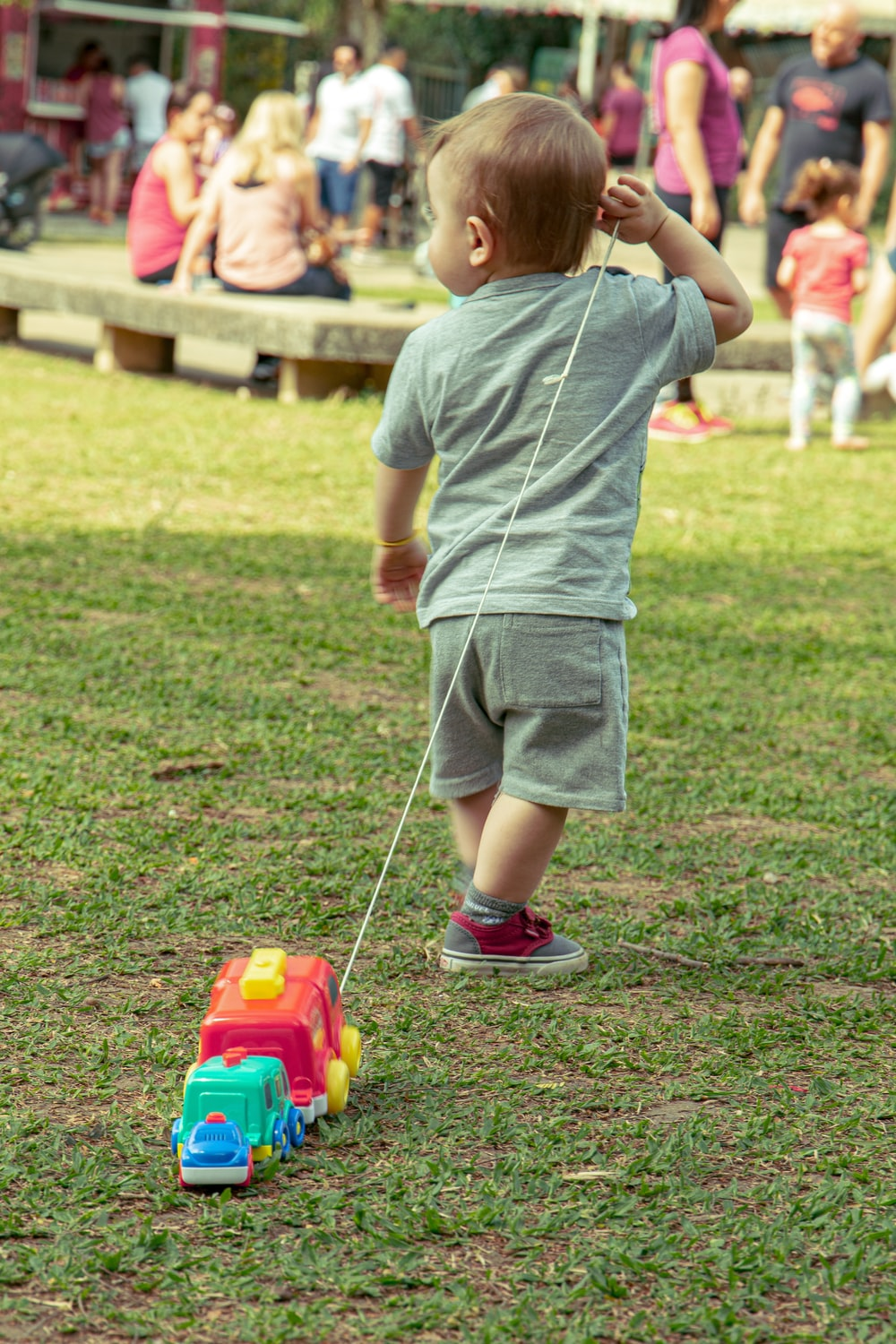 boy in grey t-shirt and grey shorts playing with red and yellow toy car on on on on on