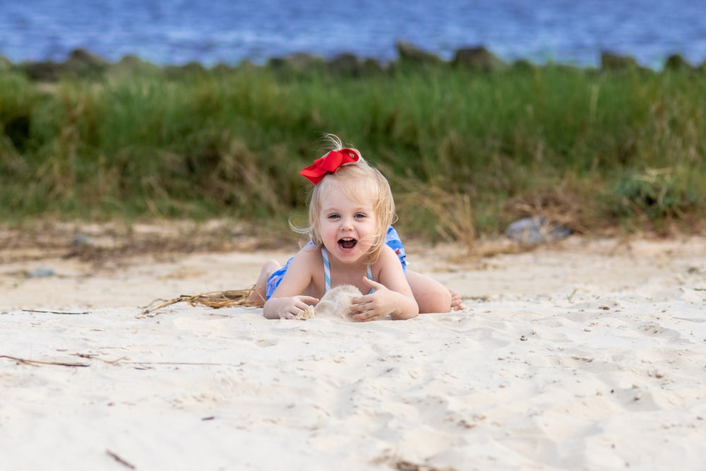 girl in red headband sitting on sand during daytime