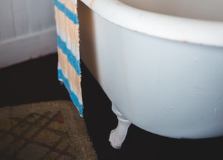 white ceramic bathtub with blue and white checked towel