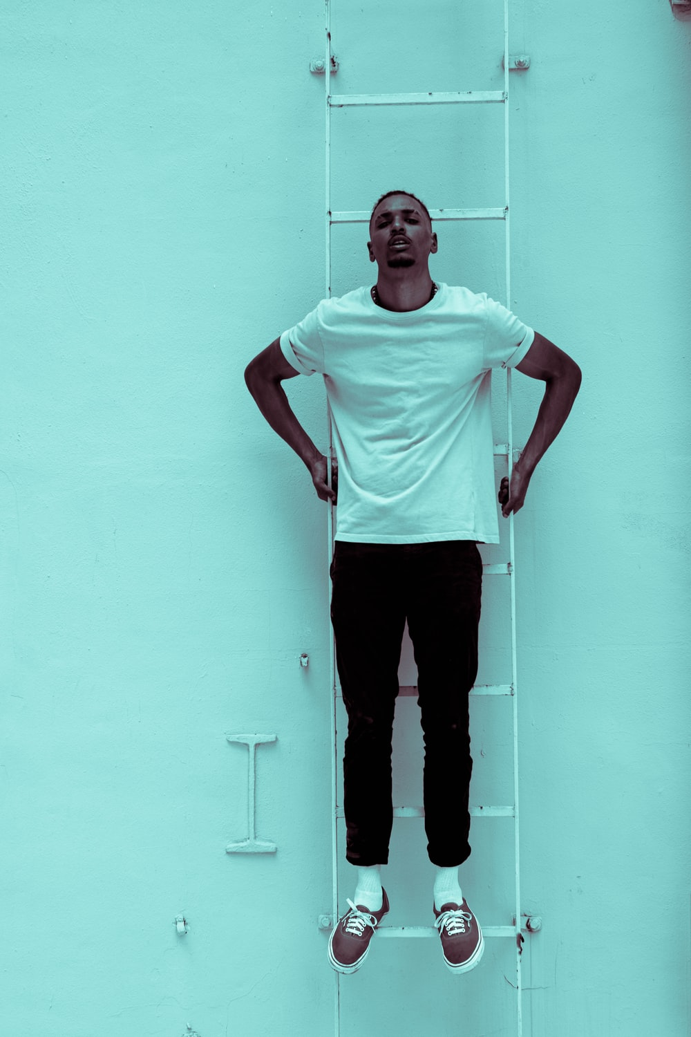 man in white crew neck t-shirt and black pants standing beside white wall