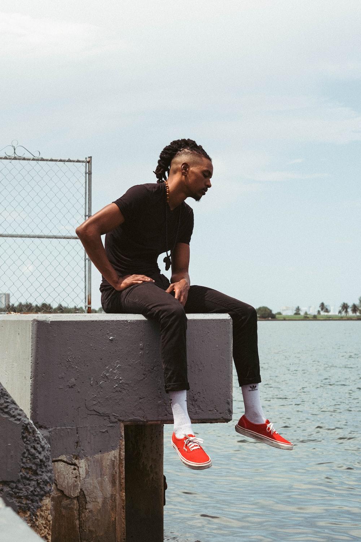 man in black crew neck t-shirt sitting on gray concrete bench