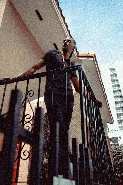 man in black t-shirt and black pants standing on black metal railings during daytime