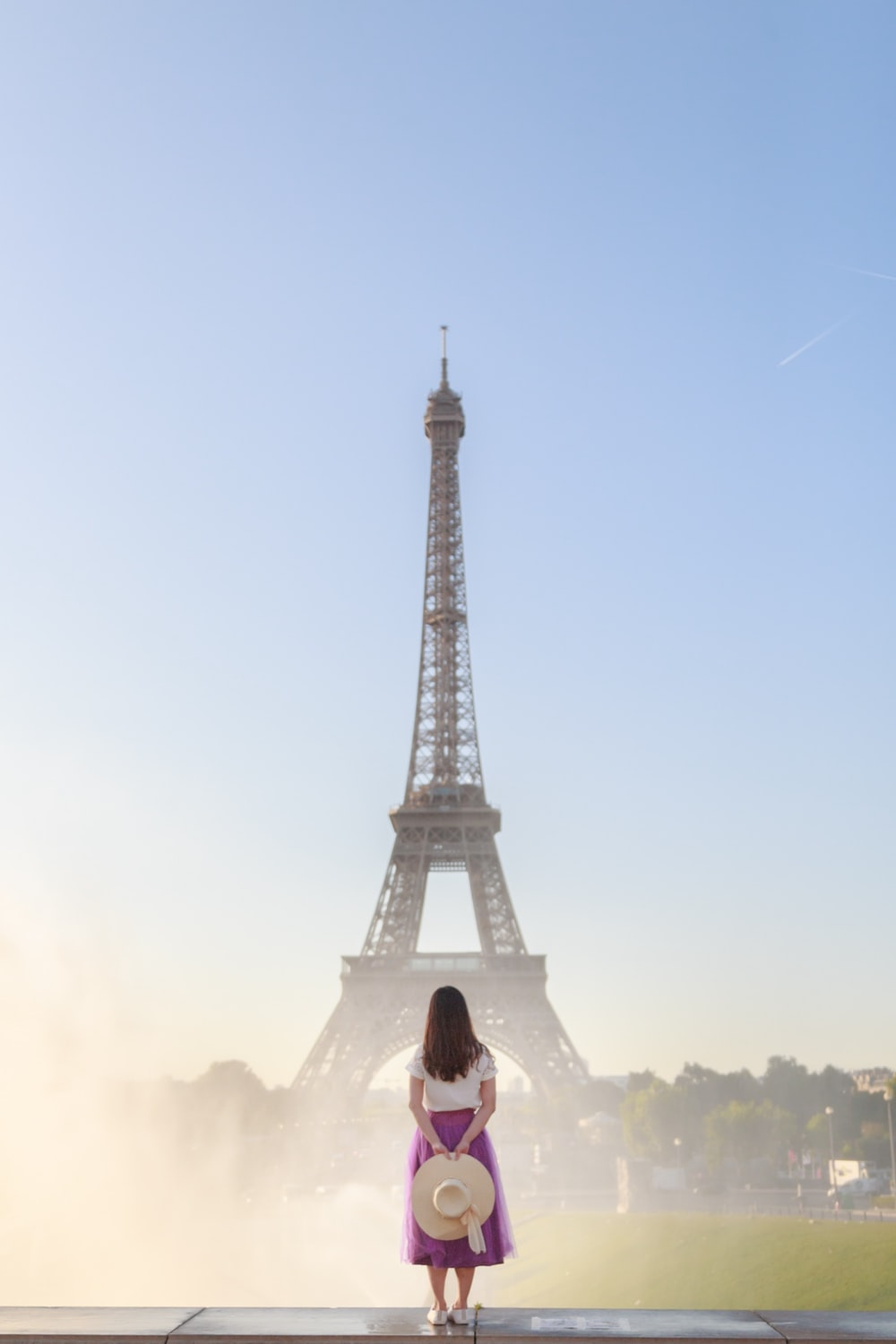 woman in white shirt sitting on the ground near eiffel tower during daytime