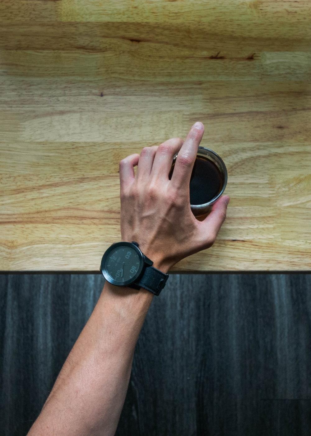 person wearing black round watch