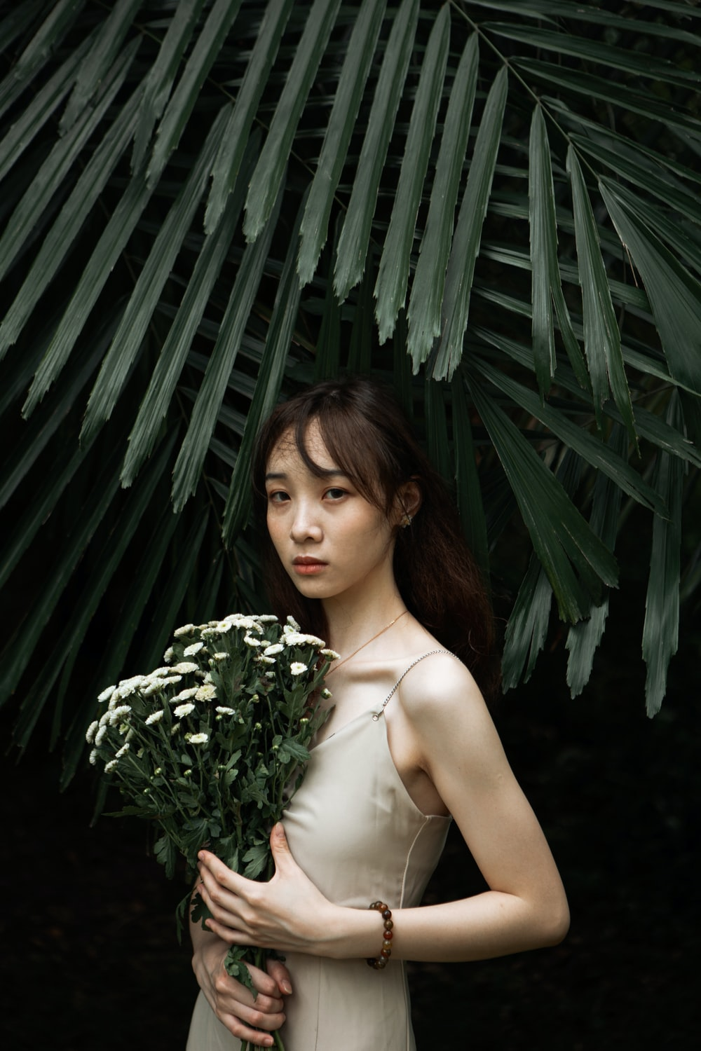 woman in white spaghetti strap top standing beside green plant