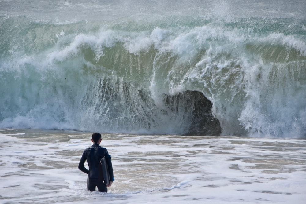 man in black jacket standing on sea shore