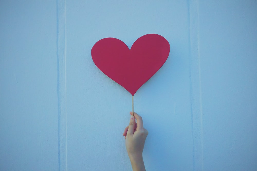 person holding heart shaped red balloon