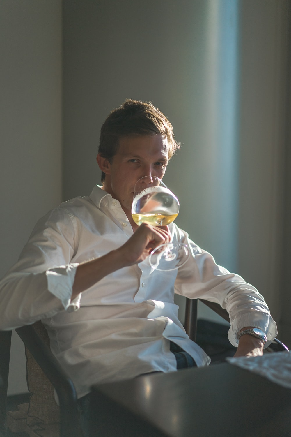 man in white dress shirt drinking from clear glass cup