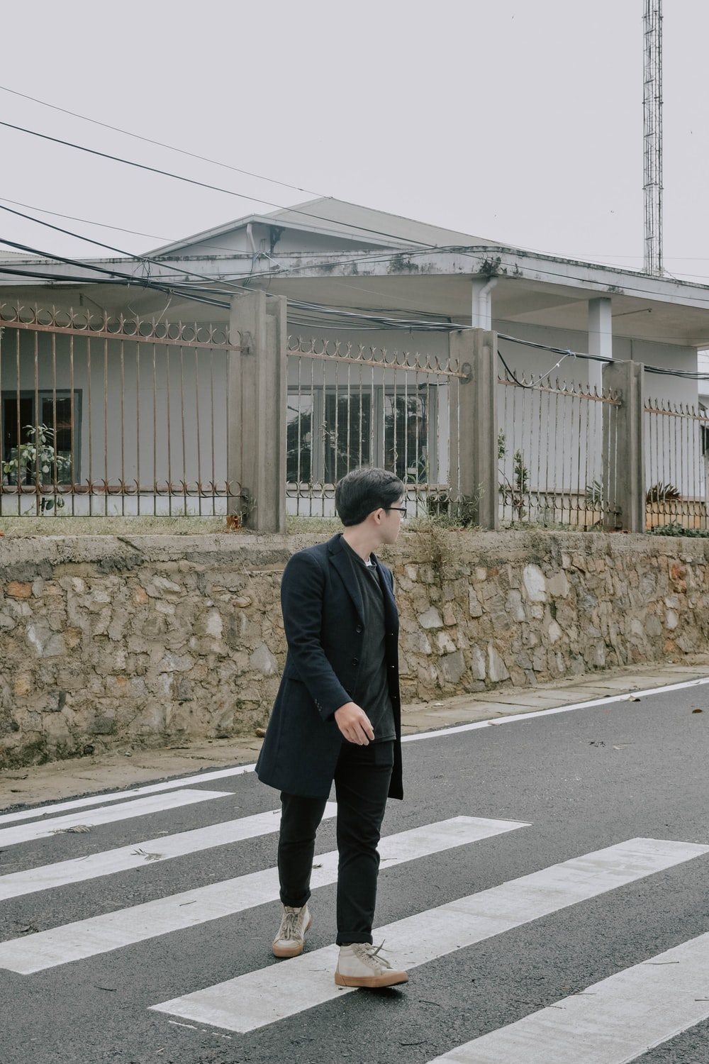 man in black coat standing on gray concrete pavement during daytime