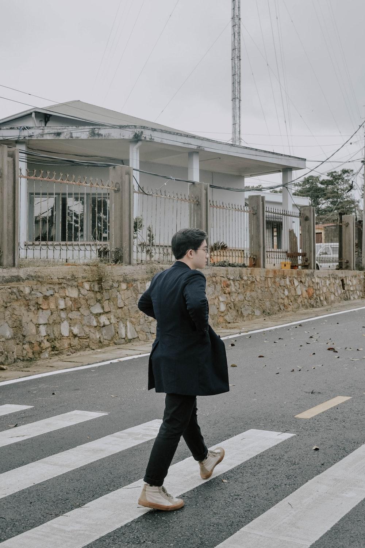 man in black coat standing on pedestrian lane during daytime