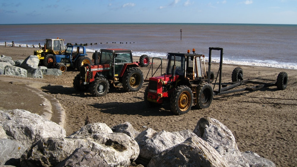 red tractor on gray sand during daytime