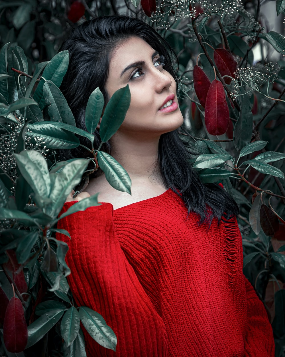woman in red knit sweater holding green leaves