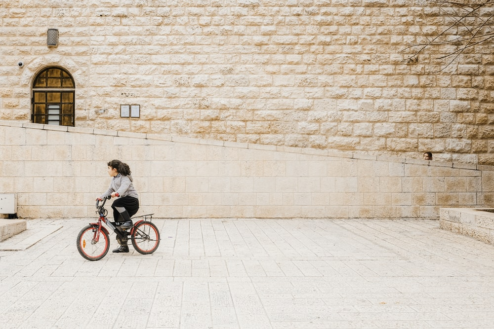 woman in black jacket riding on bicycle near brick wall during daytime